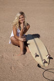 White dress sit by surf board smile Royalty Free Stock Photography
