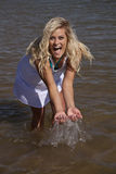 White dress splash look. A woman is looking and splashing water while she laughs Stock Image