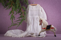 White dress, toy wooden horse and branch of christmas tree Royalty Free Stock Images