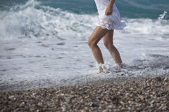 White dress, woman legs walking on tropical beach vacation. Closeup of female young adult lower body relaxing in ocean water on su Stock Photography