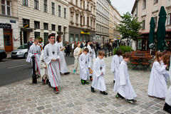 White dressed children on the road to the Catholic Church. Children and the priests go to the service of the Catholic Church on May 29, 2013 in Vienna, Austria Royalty Free Stock Photos