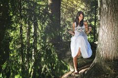 White dressed girl in evergreen summer forest Royalty Free Stock Photos