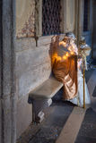 White Dressed Mask Figure sitting on the Bench near Doge`s Palac. VENICE, ITALY - FEBRUARY 7, 2016: White Dressed Mask Figure in Venice, Italy. The Venice royalty free stock images