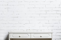 White dresser on the white brick wall. The empty dresser on the wall in the composition of a white bricks Stock Images