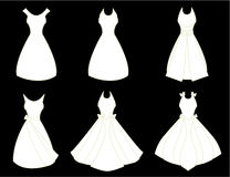 White dresses. A set of white fancy dresses isolated on a black background royalty free illustration