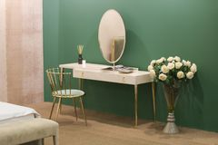 White dressing table with wicker elements, a room with a green wall and golden brass furniture, luxury mirror, female boudoir royalty free stock photos