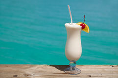 White drink by turquoise sea. Glass with a cold drink at a beach Royalty Free Stock Photo
