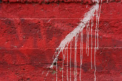 White dripping paint on vivid red concrete wall 1 Royalty Free Stock Image