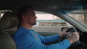 White driver in blue shirt drives car passing by overpass in beautiful backlight. Rimantic view with sunset. White driver in blue shirt drives car passing by stock video