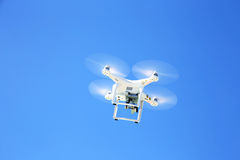 White drone  flying with camera record liens against blue sky Stock Image