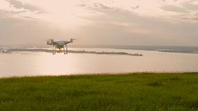 The white drone flying over the hill with green grass and is removed into the distance at sunset stock video footage