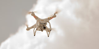 White Drone on a Grey Day. A white drone flies while camera films below on a cloudy day. Photo taken July 21, 2015 Stock Photo