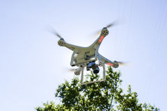 White drone hovering in a bright blue sky bottom view Stock Images