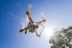 White drone hovering in a bright blue sky bottom view Stock Photo