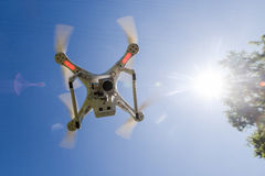 White drone hovering in a bright blue sky bottom view Royalty Free Stock Photos