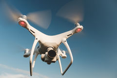 White drone hovering in a bright blue sky. Drone copter flying with digital camera stock photos