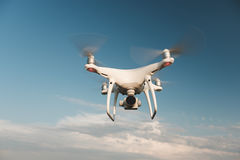 White drone hovering in a bright blue sky. Drone copter flying with digital camera royalty free stock photography