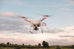 White drone hovering in a bright blue sky. Drone copter flying with digital camera stock image