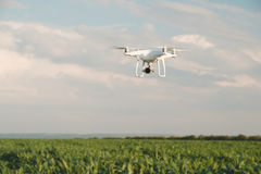 White drone hovering in a bright blue sky. Drone copter flying with digital camera royalty free stock images