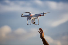 White drone hovering in a bright blue sky with hand ready to cat Stock Image