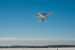 White drone quad copter with flying in the blue sky.  Stock Photos