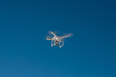 White drone quad copter with flying in the blue sky.  Stock Images