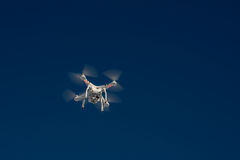 White drone quad copter with flying in the blue sky Royalty Free Stock Photos