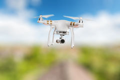 White drone quad copter with 4K digital camera flying. Royalty Free Stock Image