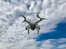 White Drone quadcopter With Blue Sky and Clouds stock photos