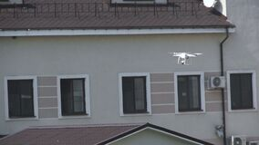 White drone, quadrocopter with photo camera flying concept. Make a video to spy stock video footage