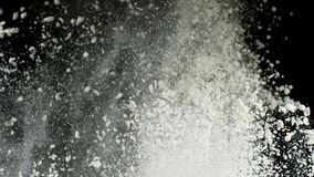 White dry powder explosion with white dust falling down isolated on black background. Stock footage. Close up for white royalty free stock photography