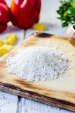 White dry rice over kitchen board with some vegetables and pasta around. Royalty Free Stock Image