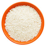 White dry uncooked grain rice. In orange bowl on white background royalty free stock photography