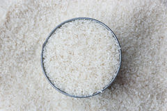 White dry uncooked rice. Close up, white dry uncooked rice heap in bowl top view surface Royalty Free Stock Photography