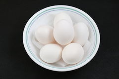 White duck eggs in white bowl in black background Stock Images