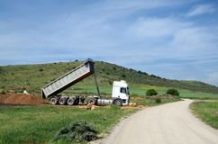 White dump truck and landscape. With road and sky with white clouds Royalty Free Stock Images