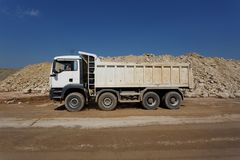 A white dump truck, lorry full of stones in a sand quarry, transporting of materials on a natural background. A white dump truck, a lorry with stones in a sand Royalty Free Stock Photo