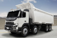 White dump truck on the road. Image of a big white dump truck with on the road under blue sky Stock Photos