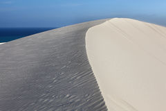 White Dunes with blue sky. And sea stock image
