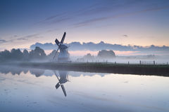 White Dutch windmill by river in misty sunrise Stock Photos