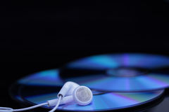 White ear phones on CDs Stock Photos