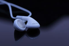 White ear phones on dark reflective background Royalty Free Stock Photos