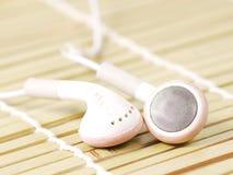 White earphone. On baboo mat Stock Image