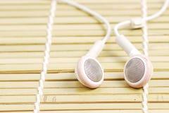 White earphone on baboo mat. Old white earphone on baboo mat Stock Photo