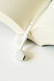 White earphone book. White earphone with book on the table Royalty Free Stock Photography