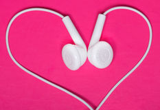 White earphone on pink background, heart Royalty Free Stock Images