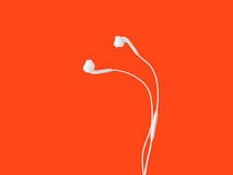 White earphone on table. White earphone for smartphone isolated on orange background Stock Image
