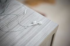 White earphone on the wooden table royalty free stock image