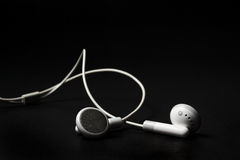 White earphones. For mp3-player on black background royalty free stock photos