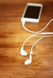 White earphones attached to smartphone. selective focus on earphones Royalty Free Stock Image